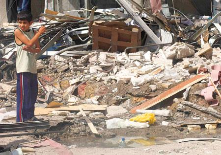 صبي يقف أمام بناء مدمر في محافظة الرقة - أرشيف