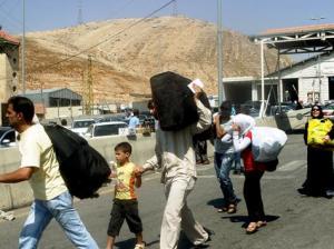 لاجئون سوريون لحظة دخولهم إلى لبنان عند نقطة المصنعة الحدودية