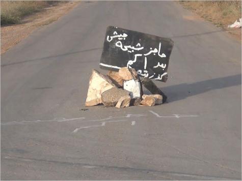 لافتة تحذر من حاجز للشبيحة على طريق كفرزيتا